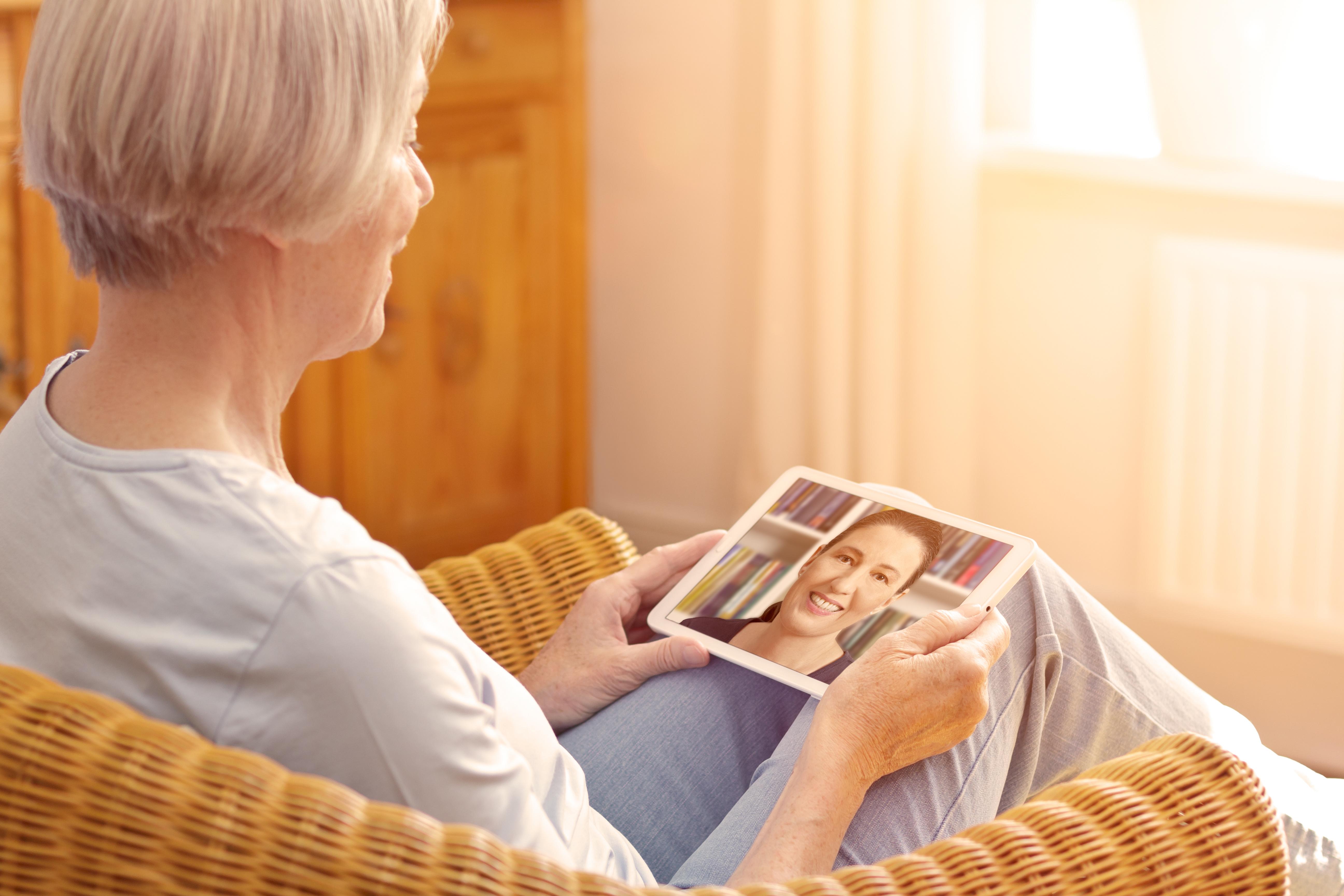 older adult woman Facetiming her daughter on tablet