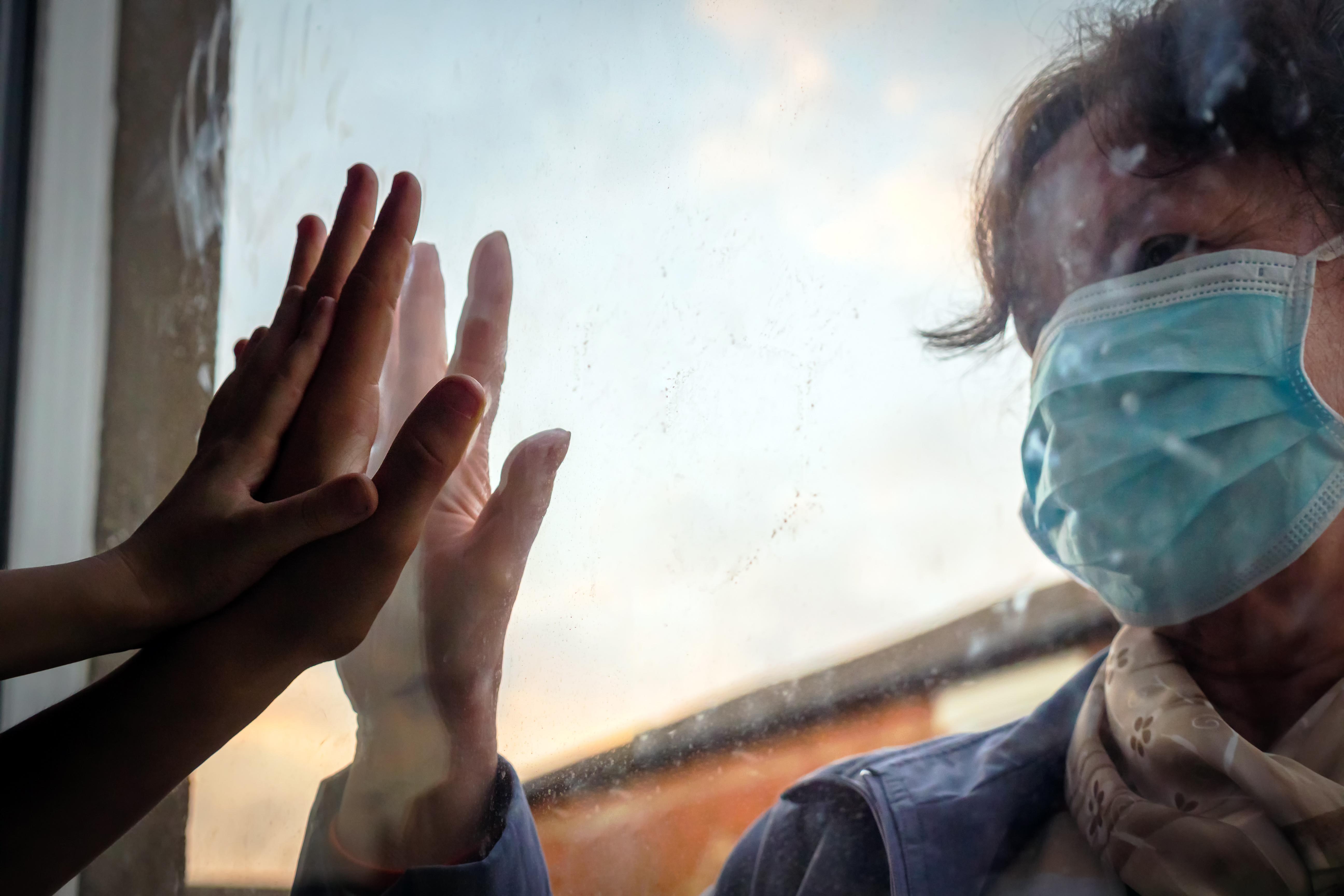 woman with mask reaching toward grandchildren's hands through a windowpane