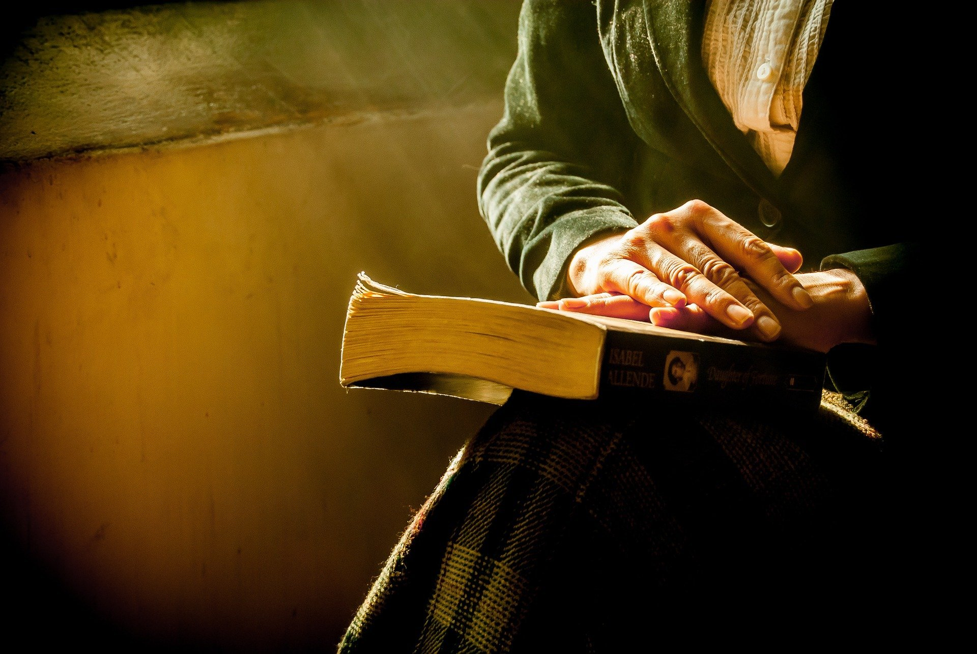 woman's hands crossed on a Bible