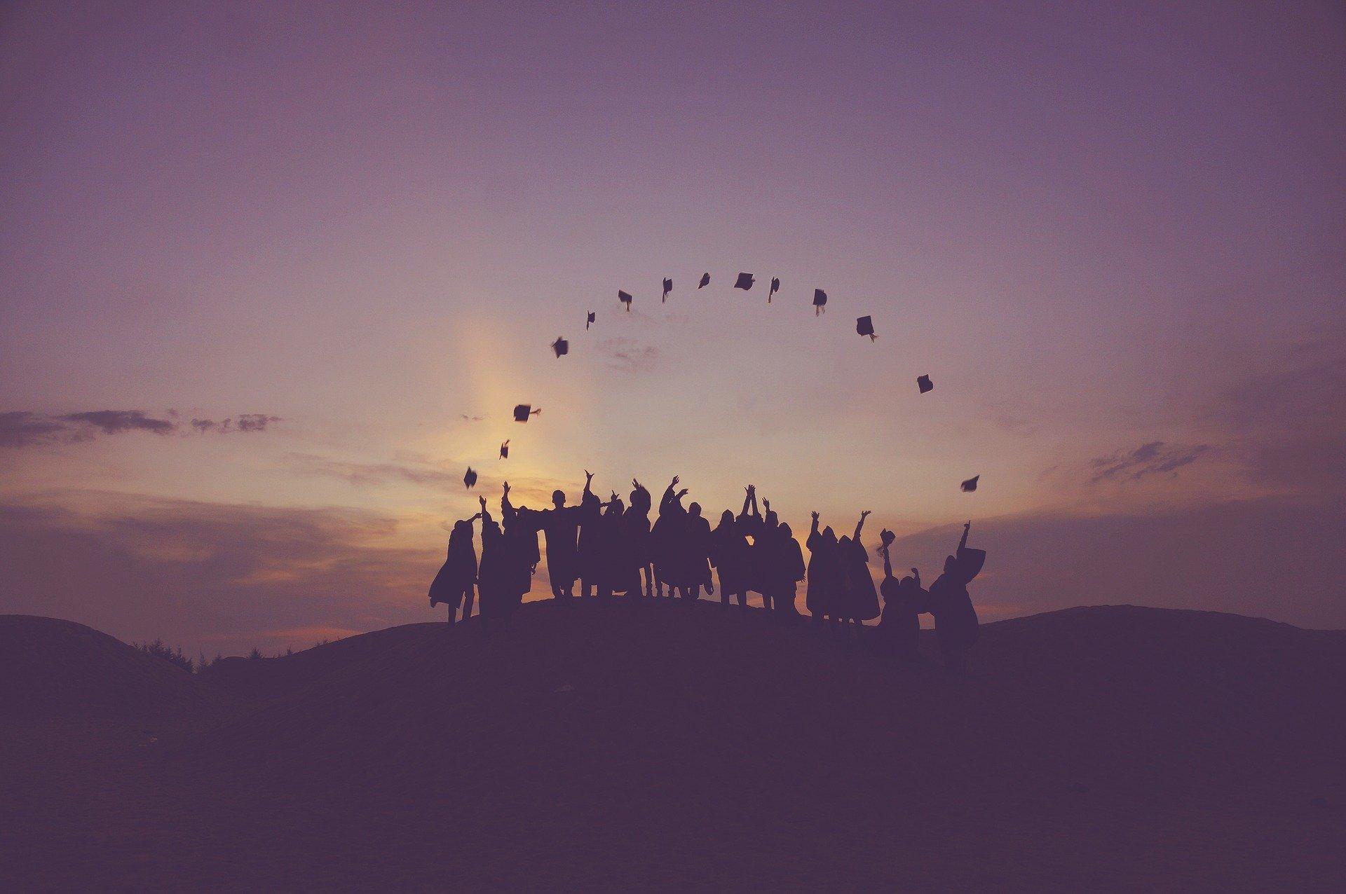 graduates tossing hats at dusk