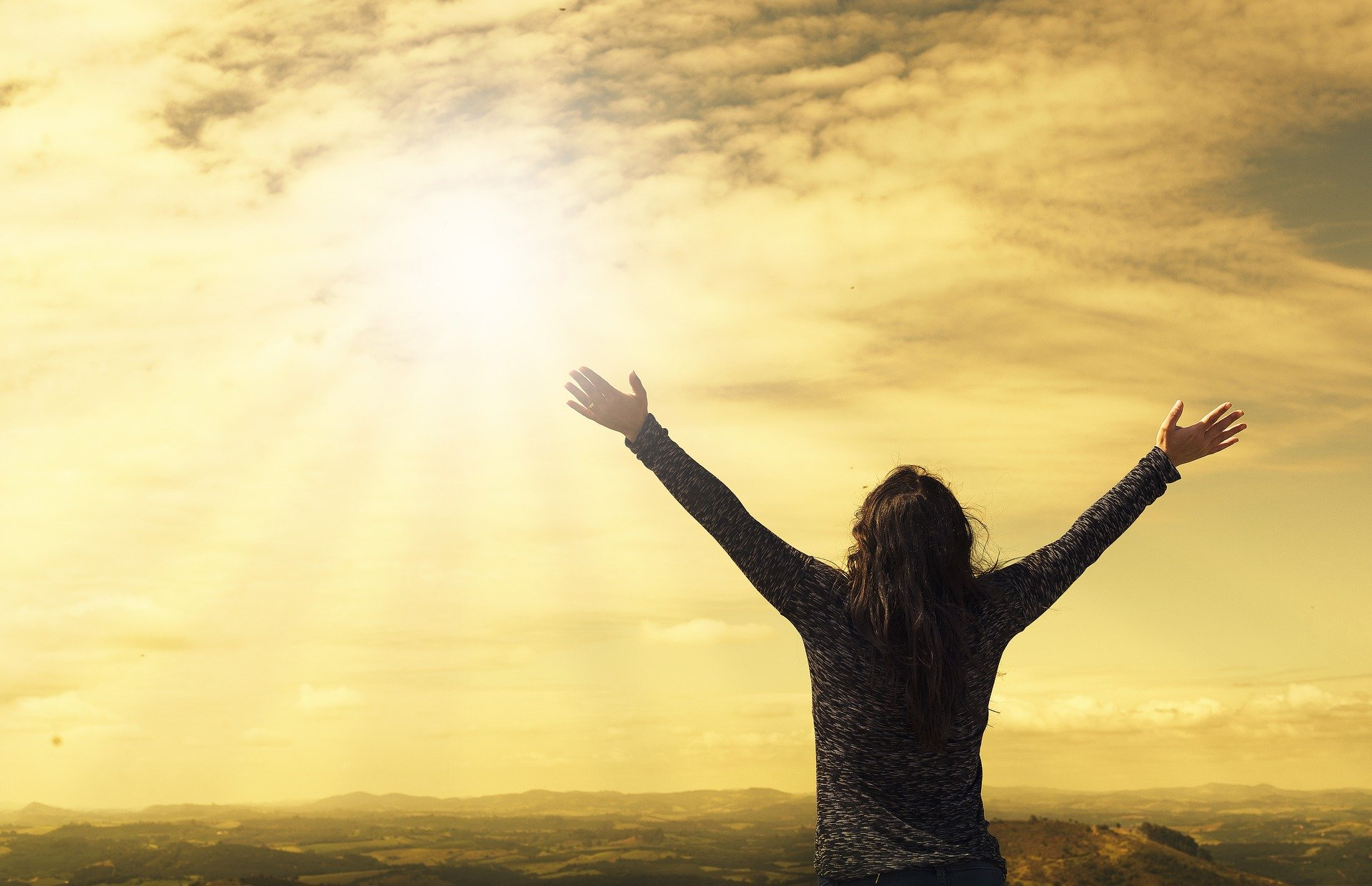 arms raised in V formation, lifted up to the sun -- hope